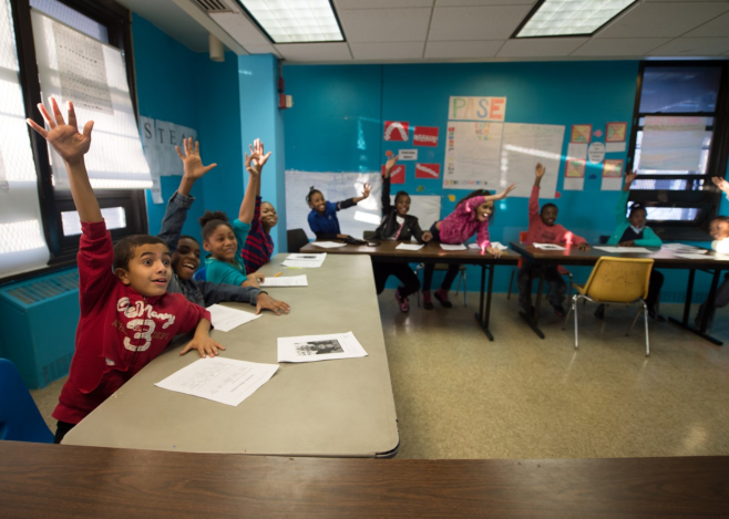 kids raising hands during class discussion